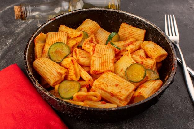 Una vista frontale ha cucinato la pasta italiana con salsa di pomodoro e cetriolo all'interno della padella sulla superficie scura