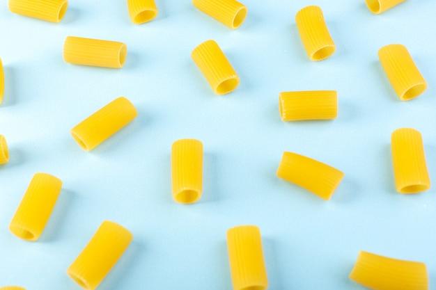 Una vista frontale ha isolato la pasta gialla poco cruda sulla pasta blu degli spaghetti del pasto dell'alimento del fondo