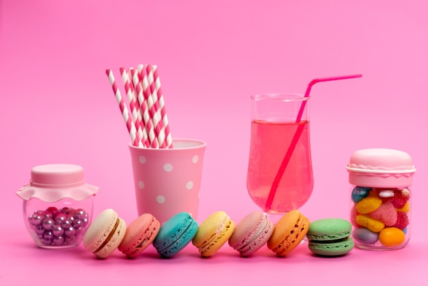 Una vista frontale macarons francesi con cannucce di succo e caramelle stick insieme a caramelle colorate su rosa, colore pasticceria biscotto torta