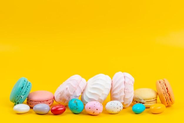 Una vista frontale meringhe e macarons deliziosi e dolci su caramelle arcobaleno di colore giallo