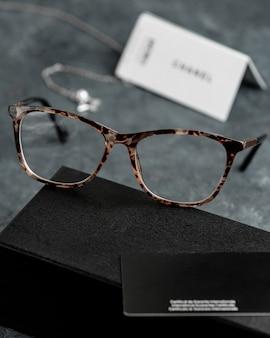 Una vista frontale occhiali da sole ottici sulla scrivania grigia con bracciali d'argento isolato gli occhi di visione a vista