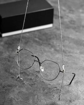 Una vista frontale occhiali da sole ottici sulla scrivania grigia con catene d'argento isolato gli occhi di visione a vista
