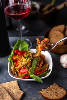 Una vista frontale patate fritte insieme con verdure a fette foglie verdi all'interno del piatto bianco insieme a patatine vino rosso sulla scrivania grigia vitamine verdure