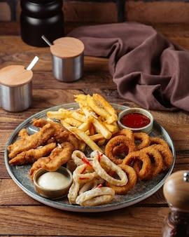 Una vista frontale patatine fritte con ali di pollo fritte e anelli di cipolla con ketchup sulla patata pasto cibo scrivania in legno marrone