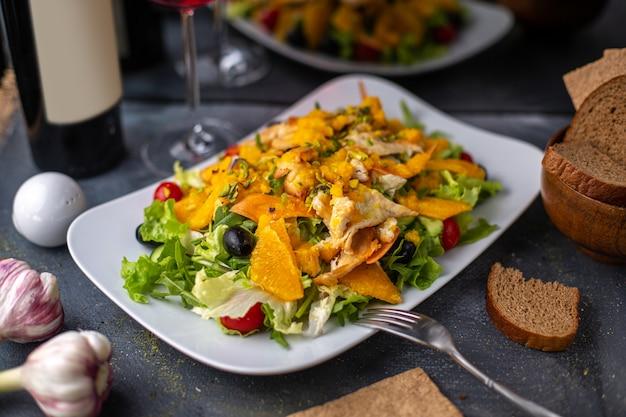 Una vista frontale patatine fritte con verdure a fette verdi all'interno del piatto bianco salato pepato insieme con patatine di vino rosso sui piatti della cena scrivania grigia
