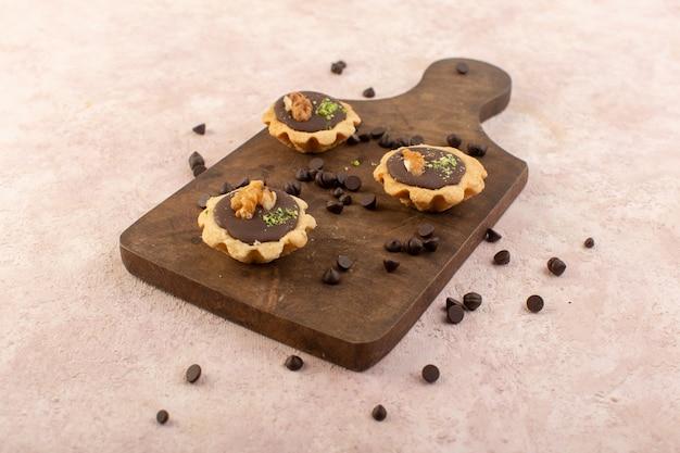 Una vista frontale piccole torte al cioccolato buonissime e deliziose sulla scrivania in legno