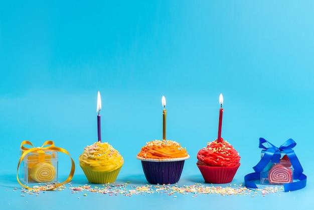 Una vista frontale piccole torte colorate con candele e fiocchi su blu,