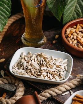 Una vista frontale semi bianchi salati con noci sul seme di spuntino dado tavolo in legno