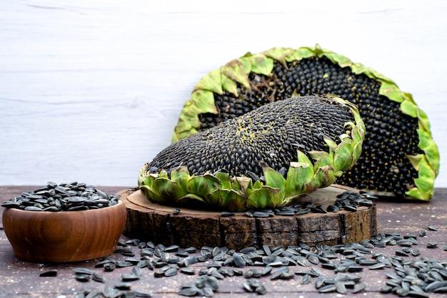 Una vista frontale semi di girasole neri freschi e gustosi sull'olio snack di semi di grano marrone scrivania