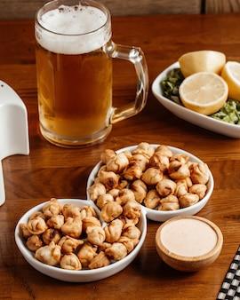 Una vista frontale spuntini fritti con sale, limone e birra sullo spuntino del pasto alimentare dello scrittorio di legno marrone