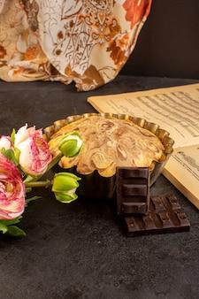 Una vista frontale torta rotonda dolce squisita deliziosa all'interno della tortiera insieme a choco bar fiori e note musicali quaderno sullo sfondo grigio biscotto di zucchero biscotto