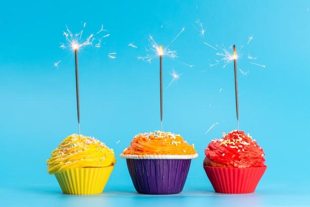 Una vista frontale torte colorate deliziose su blu, colore festa di compleanno