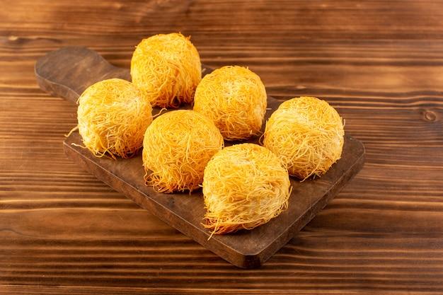 Una vista frontale torte dolci deliziosi gustosi dolci isolati allineati sulla scrivania in legno marrone marrone e marrone