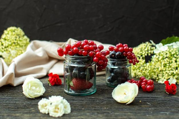 Una vista frontale vicino bacche fresche come more e mirtilli all'interno di lattine di vetro intorno a fiori bianchi sul pavimento di legno grigio