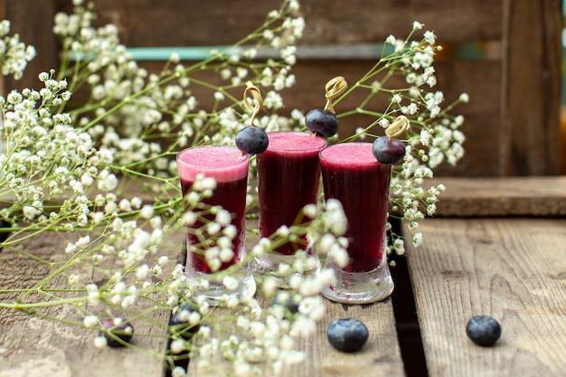 Una vista frontale vicino vista cocktail freschi intorno a fiori e sulla superficie di legno marrone