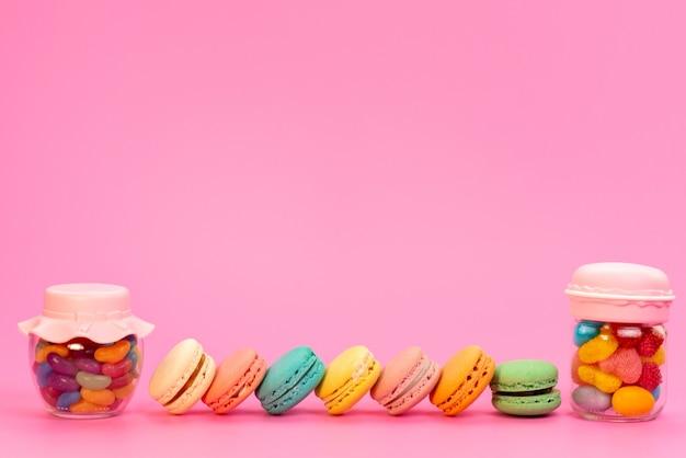 Una vista frotn francese macarons insieme a caramelle multicolori all'interno di lattine sul rosa
