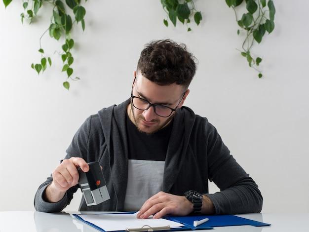 Una vista frotn giovane attraente uomo in giacca grigia occhiali da sole lavorando con documenti sul pavimento bianco