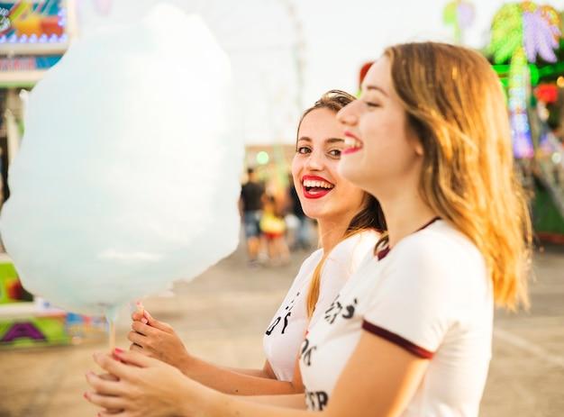 Una vista laterale di due amici femminili felici che tengono il filo di caramella blu