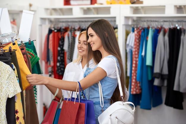 Una vista laterale di due donne che scelgono i nuovi vestiti in centro commerciale