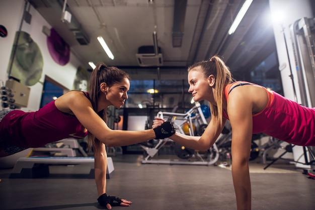 Una vista laterale di due giovani womans attivi sportivi sani attraenti motivati che fanno esercizi push up e riscaldamento sul pavimento mentre si tengono le mani insieme in palestra.