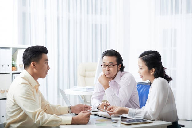 Una vista laterale di tre colleghi che discutono del progetto seduto alla scrivania