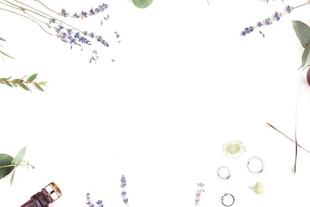 Una vista piana e superiore di una scrivania da ufficio. cornice di un tavolo di lavoro di un tavolo femminile con i colori di una lavanda, ore, punti e anelli d'argento. disteso. vista dall'alto.