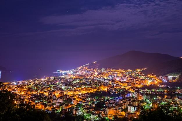 Una vista pittoresca della città notturna dalla cima della montagna.