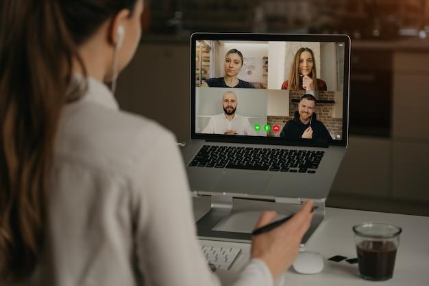 Una vista posteriore di una donna che lavora da remoto in una videoconferenza con i suoi colleghi durante una riunione online. partner in una videochiamata. squadra multietnica di affari che ha una discussione in una riunione online