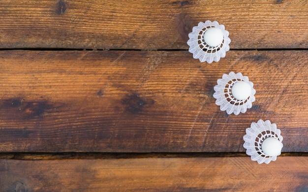 Una vista sopraelevata di tre shuttlecocks bianchi sul fondo di legno della plancia