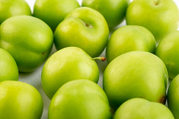 Una vista superiore chiusa chiusa ciliegia-prugna verde rotondo isolato dolce fresco acido su sfondo bianco qualità della frutta