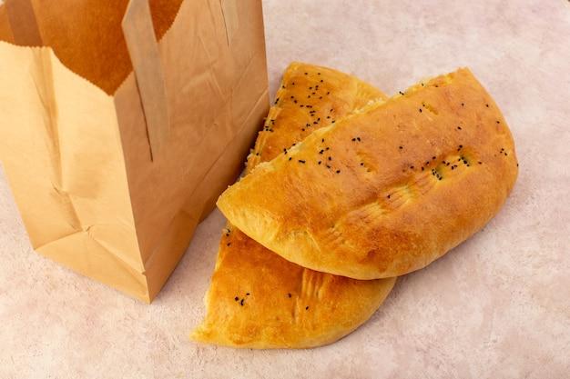 Una vista superiore del pane cotto caldo gustoso metà fresca affettata all'interno e all'esterno dei pacchetti di carta sul rosa