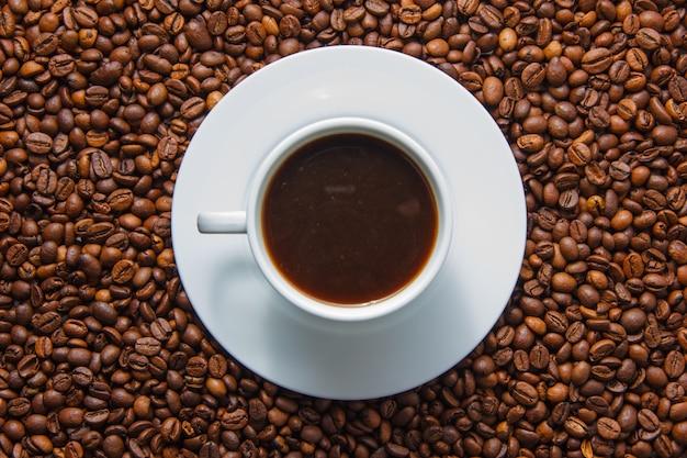 Una vista superiore della tazza di caffè con i chicchi di caffè su fondo