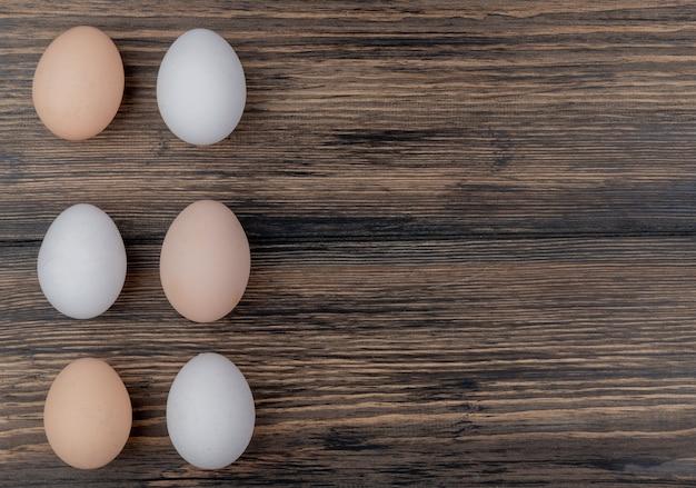 Una vista superiore di sei uova di gallina disposte su uno sfondo di legno con copia spazio