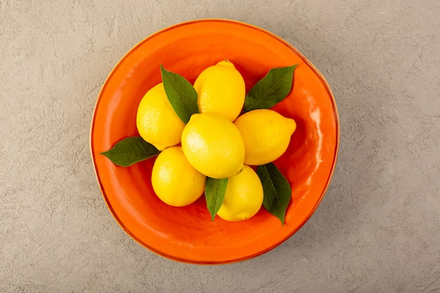 Una vista superiore giallo limoni freschi maturi dolce succosa all'interno piatto arancione su sfondo grigio frutti colore agrumi