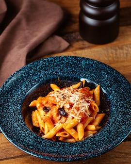 Una vista superiore ha cucinato la pasta italiana con la salsa sul pasto dell'alimento del cuoco della pasta della tavola di legno marrone