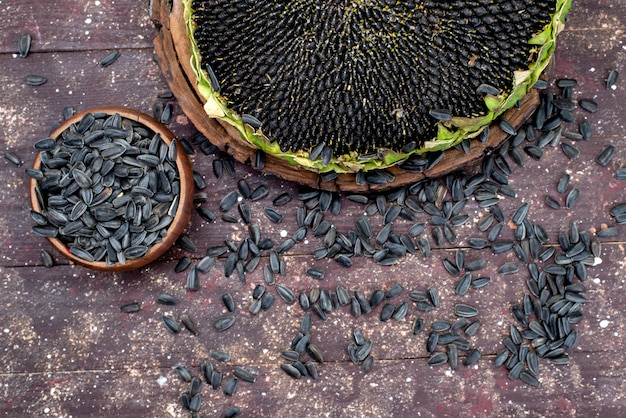 Una vista superiore semi di girasole neri freschi e gustosi sullo spuntino marrone del seme di girasole del grano del fondo