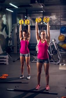 Una vista verticale di due giovani womans attivi di forma fisica attraente attraente motivata motivata che fanno gli esercizi con i pesi mentre avendo alzato le armi nella palestra moderna.