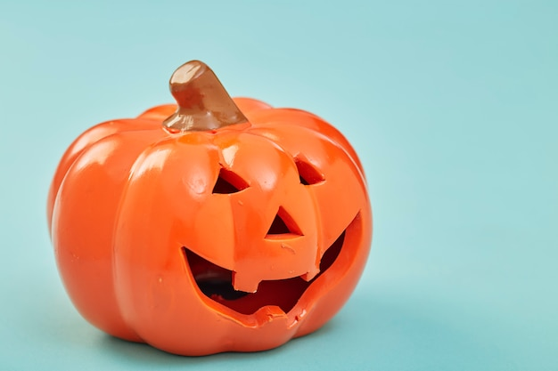 Una zucca di halloween su sfondo blu pastello