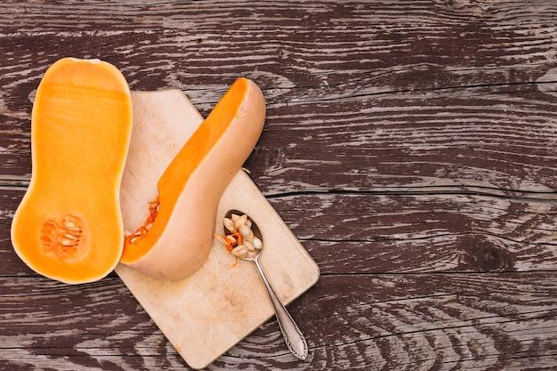 Una zucca e semi organici sul cucchiaio sopra il tagliere contro lo scrittorio di legno