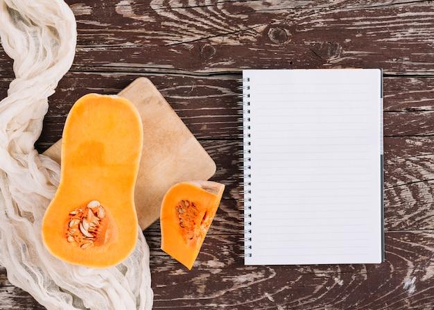 Una zucca torta organica sul panno e tagliere con blocco note a spirale sulla scrivania in legno