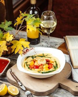 Una zuppa con noodles e bicchiere di vino