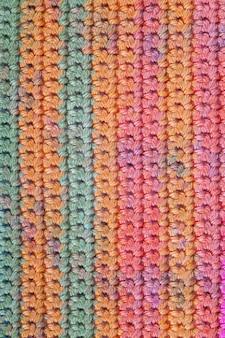 Uncinetto, fatto a mano, cucito. vicino a macro texture di sfondo della trama a maglia a strisce.