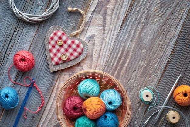 Uncinetto, vista dall'alto su gomitoli di lana su legno rustico