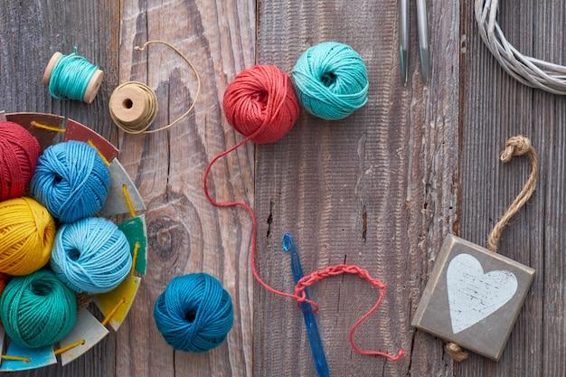 Uncinetto, vista dall'alto su gomitoli di lana su legno