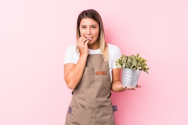 Unghie da mordere isolate giovane donna caucasica del giardiniere, nervose e molto ansiose.