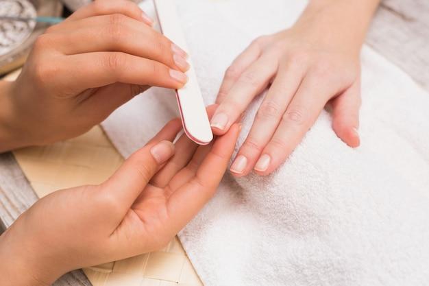 Unghie tecnico dando al cliente una manicure