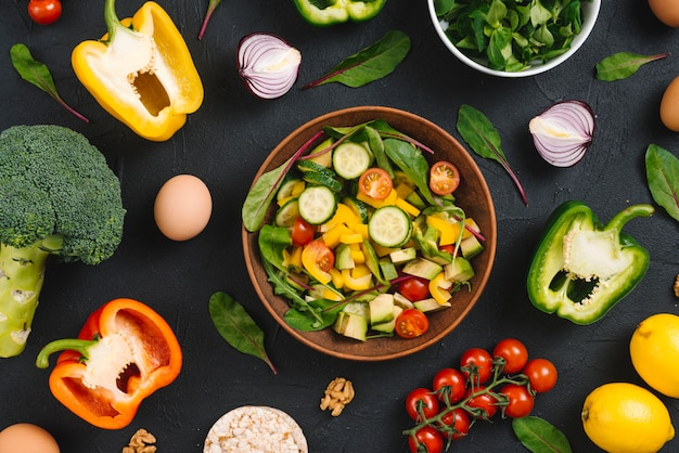Unico uovo intero e insalata mista di verdure fresche sul bancone nero