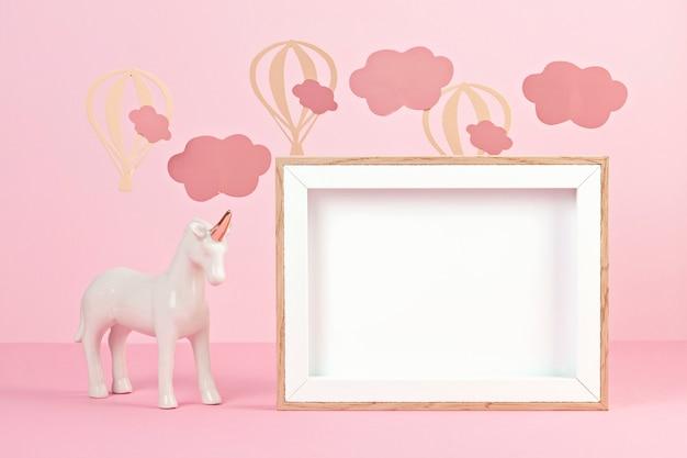 Unicorno bianco carino su sfondo rosa pastello con nuvole e palloncini