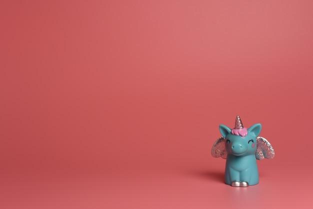 Unicorno blu con ali d'argento e capelli rosa su uno sfondo rosa