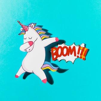 Unicorno dabatter bianco con boom di testo comico su sfondo blu